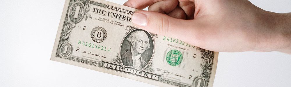 Hand holding out a one dollar bill