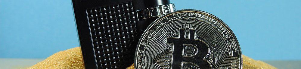 Silver bitcoin beside locked black padlock on sand
