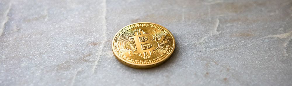 Gold bitcoin on top of marble surface