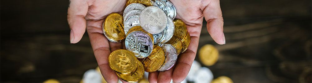 Gold and silver crypto coins in two palms