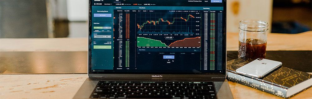 Laptop on table showing financial market trend on screen beside glass and phone