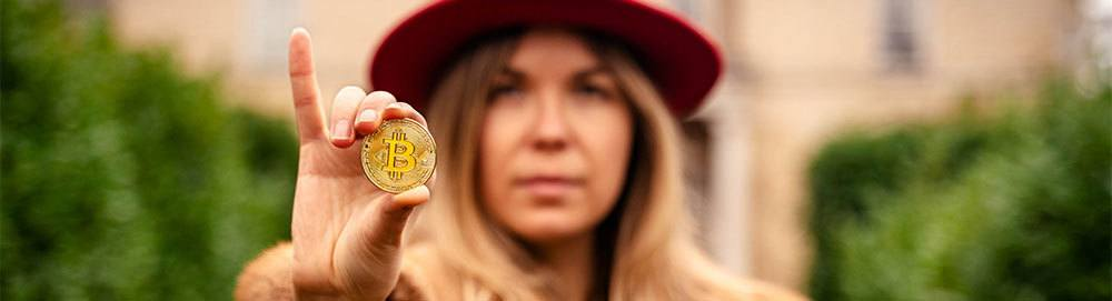 Woman wearing red hat holding out bitcoin between fingers