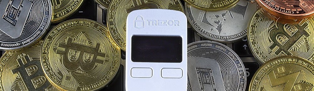 White Trezor on top of cryptocurrency coins