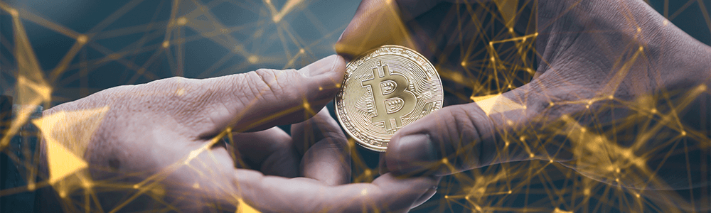 Two persons holding one Bitcoin