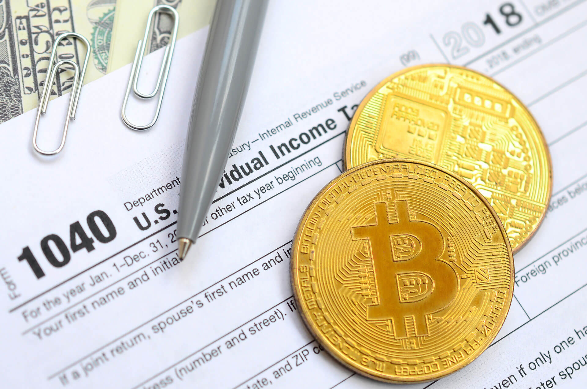 Two gold bitcoins on top of individual tax form with pen and paperclips