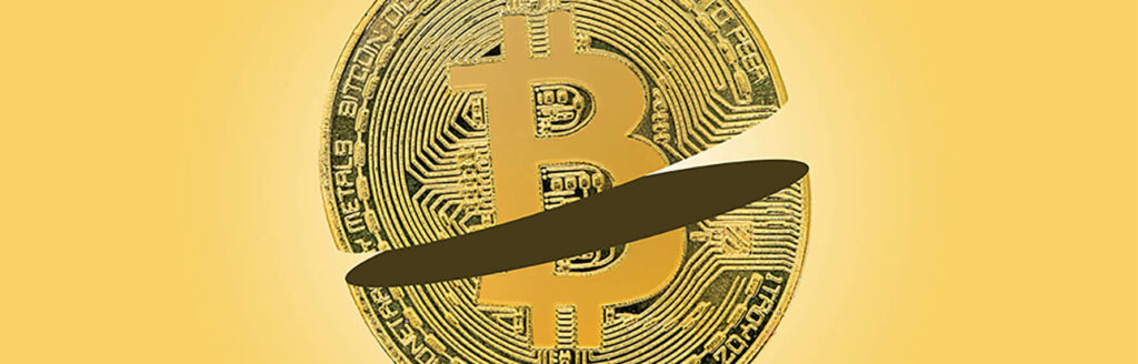 Bitcoin sliced in half on yellow background